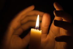 Candle fire with palms around it. Palms of a girl around candle fire in darkness Royalty Free Stock Images