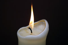Candle Flame. Close up image of a flame from a white candle set against a dark background Royalty Free Stock Photography