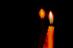 Candle flame light at night and reflection effect of the mirror with abstract black background. Stock Image