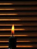 Candle Flame and Shutters. Candle flame in front of wooden shutters Stock Images