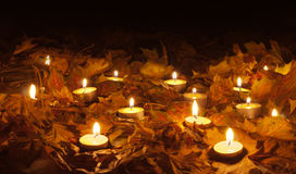 Candle flames lighting the bed of dry leaves Stock Photo