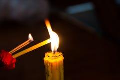 Candle a flor clara, vermelha no preto no fundo Fotografia de Stock Royalty Free