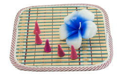 Candle flower and incense cone on bamboo mat Stock Images