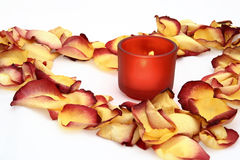 Candle and flower petals. Red wax candle and reddish flower petals arranged in the shape of a heart Stock Photos