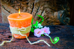 Candle and flowers plastic beautiful. On wood table Royalty Free Stock Photos