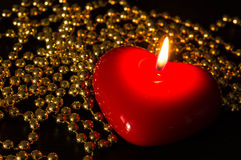 Candle in the form of heart with a gold beads Royalty Free Stock Images
