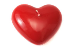 Candle in the form of red hearts on a white background royalty free stock photos