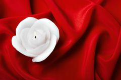 Candle in the form of a rose against red silk Royalty Free Stock Photography