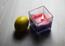 Candle with a fresh lemon on the light background royalty free stock image
