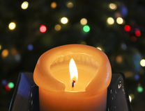 A Candle in Front of a Christmas Tree Royalty Free Stock Photo
