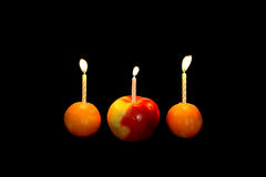 Candle in a fruit. Candle in a fruit on a black background Stock Image