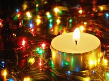 Candle and garland lights. Candlelight and colorful christmas garland lights royalty free stock images