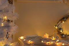 Candle, garland, wreath on a fireplace shelf and sprigs of white Christmas tree in the light of lights royalty free stock photos