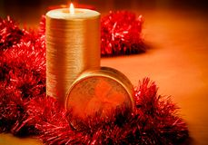 Candle and gift box with red tinsel Stock Images