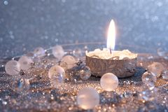 Christmas card with a burning candle on a silver background. royalty free stock image