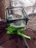 Candle in a glass candleholder with Green bow. The candle in a glass candleholder with Green bow royalty free stock image