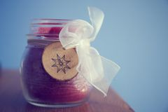Candle in glass jar plus a wooden decoration and white ribbon stock images