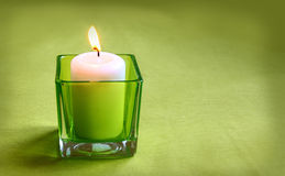 A  candle in glass lamp on a green background Stock Photos