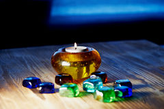Candle in glass orange  holder with colorful beads, burning. Royalty Free Stock Photos