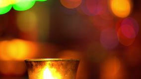 Candle in a glass stay on wooden table in blues music bar. Blurred backround. Bokeh. Colored illumination. 4K