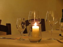 Candle and glasses on a restaurant tablle Stock Images