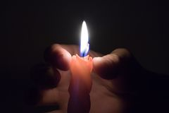 Candle in hand. Light of candle in the hand stock photography