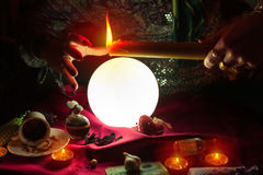 Candle in hand of fortune teller woman above crystal ball Royalty Free Stock Image
