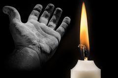 Candle and hand on the subject of death and commemoration stock photography