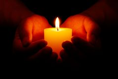 Candle in hands. Heart-shaped hands holding yellow candle in dark Royalty Free Stock Photography