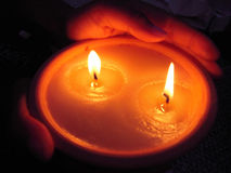 Candle on hands. Two flames, one candle in hands stock images
