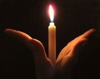 Candle in hands. On a dark background Stock Photography