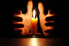 Candle in the hands. And black background Royalty Free Stock Photography