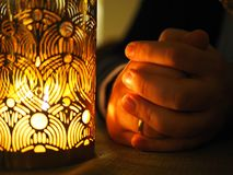 Candle and hands folded together in prayer or petition. The hands of an adult man with a wedding ring, thanksgiving. Man in prayer stock images
