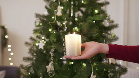Candle in the hands in front of christmas tree stock footage