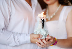 Candle in the hands. Of the newlyweds Stock Image
