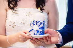 Candle in the hands of the newlyweds. royalty free stock photos