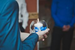 Candle in the hands of the newlyweds 6179. Young husband and wife holding a candle Royalty Free Stock Photos