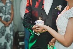 Candle in hands 2068. Wellbeing symbol in hands of the newly-married couple Stock Image