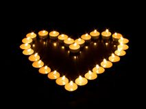 Candle hart. Burning candles forming a hart on black background stock image