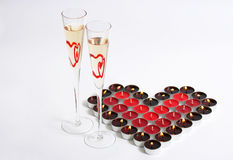 Candle Heart and Champagne. Valentine Heart made of red candles and two glasses of champagne Royalty Free Stock Image