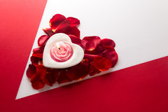 Candle heart on the heart of rose petals corner red white backgr Stock Image