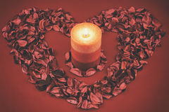 Candle in a heart of petals Royalty Free Stock Photography