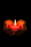 Candle in heart shape. Heart-shaped hands holding one candle in darkness Stock Photos