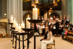 Candle holder with candles and blurred people in church stock image