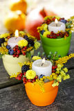 Candle holder decorated with autumn flowers Stock Photography