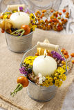 Candle holder decorated with autumn flowers and other plants. Royalty Free Stock Images