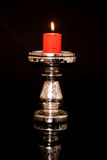 Candle And Holder. Lighted red candle in a candle holder Stock Photo