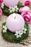 Candle holder made of moss, decorated with arabian star flowers. (ornithogalum arabicum). Pink roses in the background Stock Photos