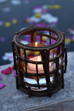 Candle in holder by pool. Candle burning in wooden holder on side of pool with floating flower petals Royalty Free Stock Photography