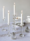 Candle holders. Various burning glass candle holders on embroidered tablecloth on white Royalty Free Stock Images